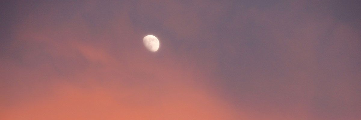 The moon through sun-blushed clouds